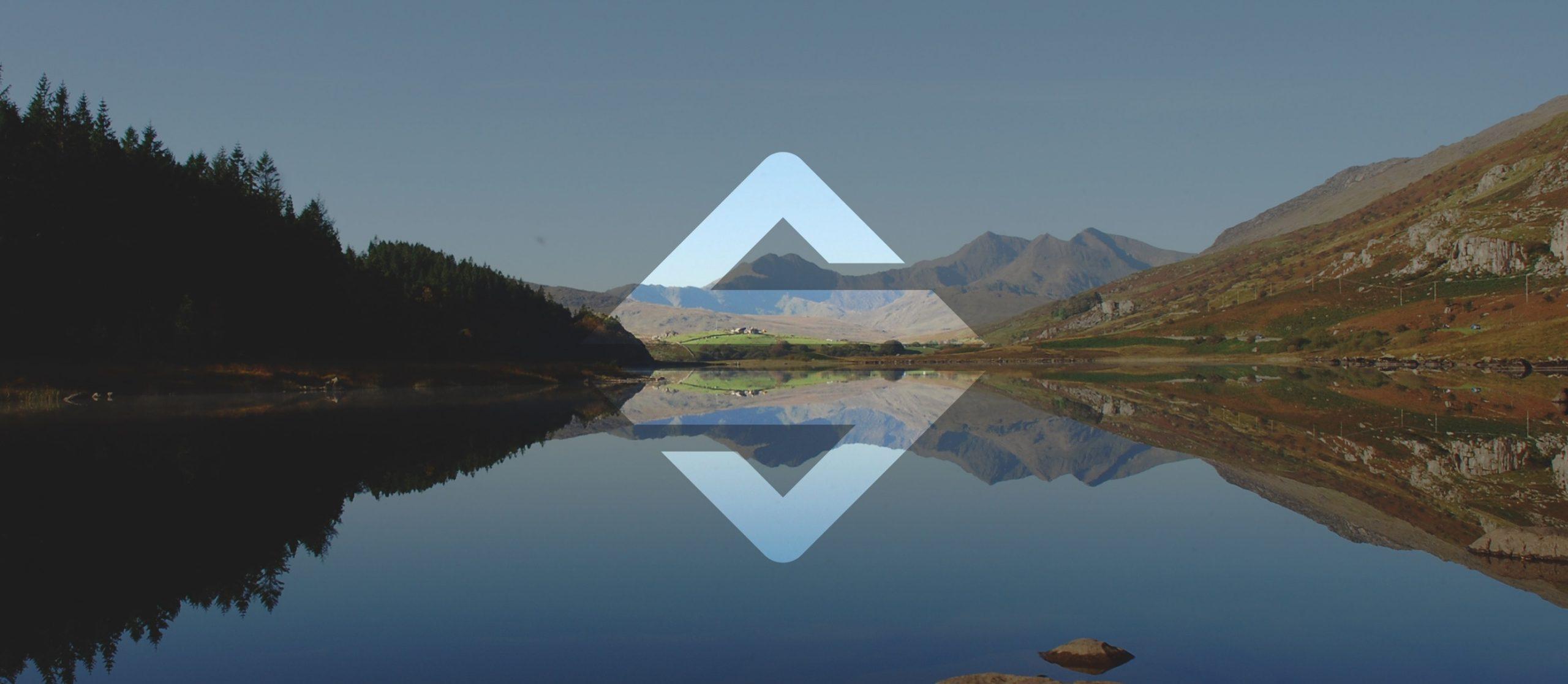Plas Y Brenin (PYB)logo overlaying a landscape