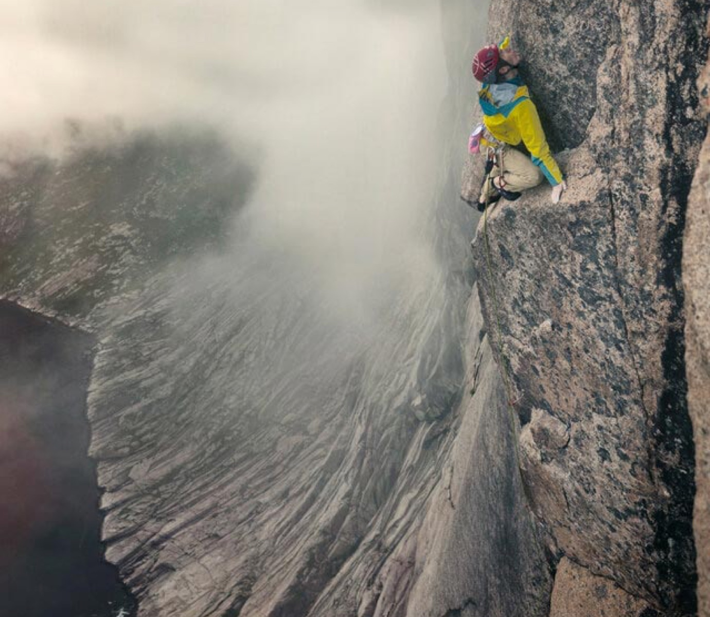 Climber high up on a mountain ledge