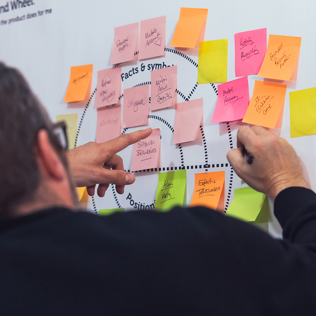 Gerry Arcari discussing post-it notes on a meeting room board